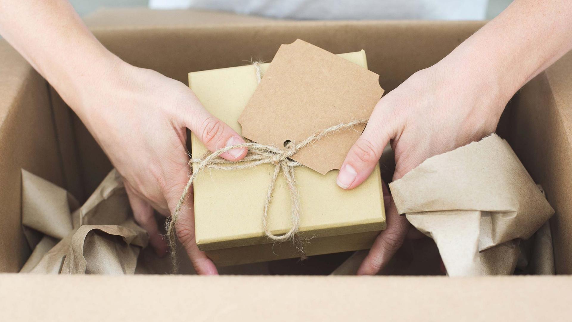 Mani di donna che aprono un pacco ricevuto tramite e-commerce B2B